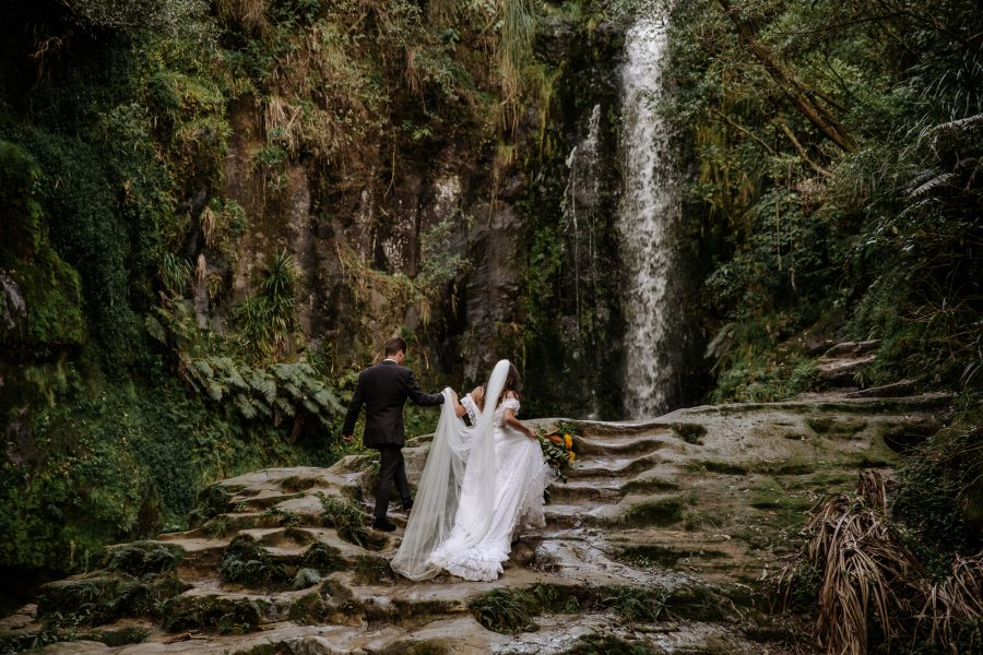 Elopement shoot at Kaiate falls with couple climbing rocks up to waterfall
