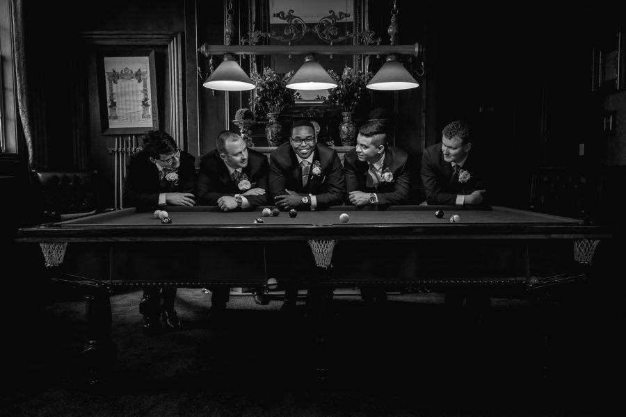 Groom with groomsmen on pool table