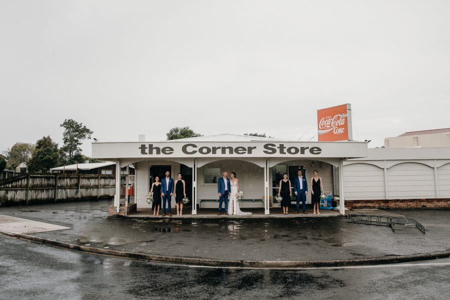 The corner store at Whangamata with wedding party in the rain