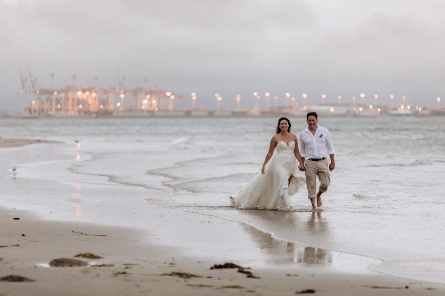 elopement wedding photos couple walking in the sea Tauranga