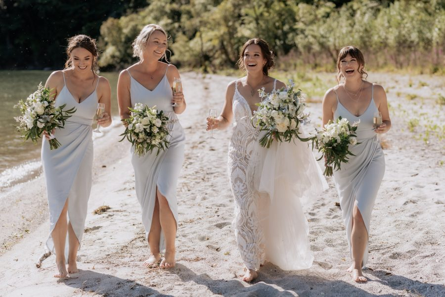 Bride with bridesmaids in grey  green bridesmaids dresses laughing having fun