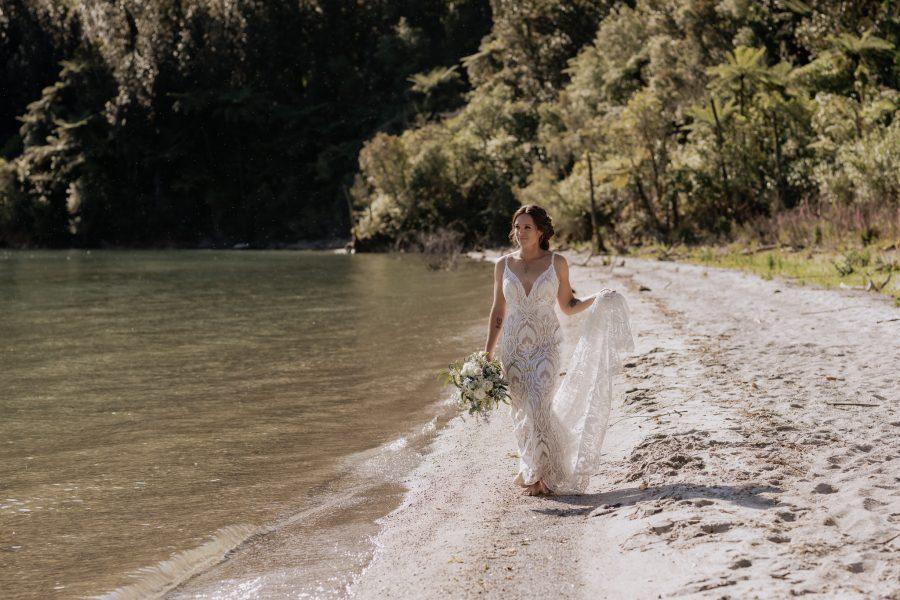 Bride in jessical bridal couture walking along lake shore in Rotorua lakes