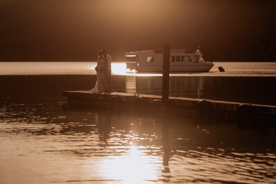 Sun setting on waters of Lake Okataina with wedding couple
