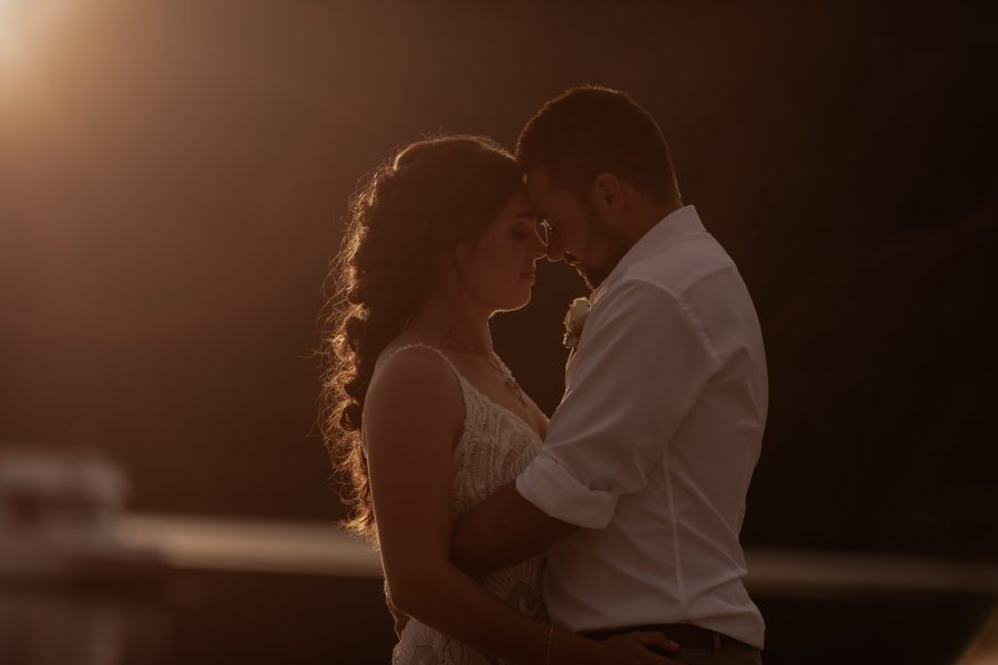 Godlen hour light hitting the hair of wedding couple while cuddling