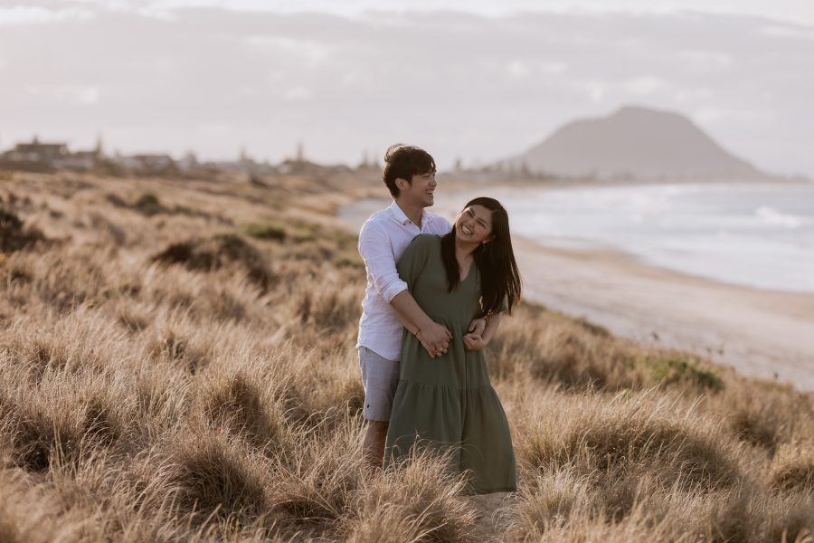 Laughing engagement photos of couple in Tauranga beach sand dunes
