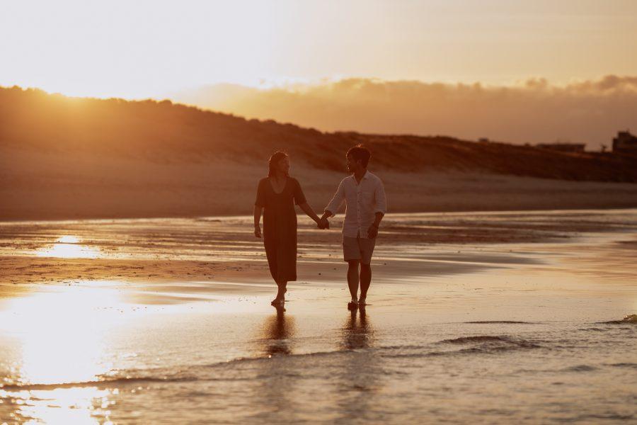 couple walking beach engagement photos sunset