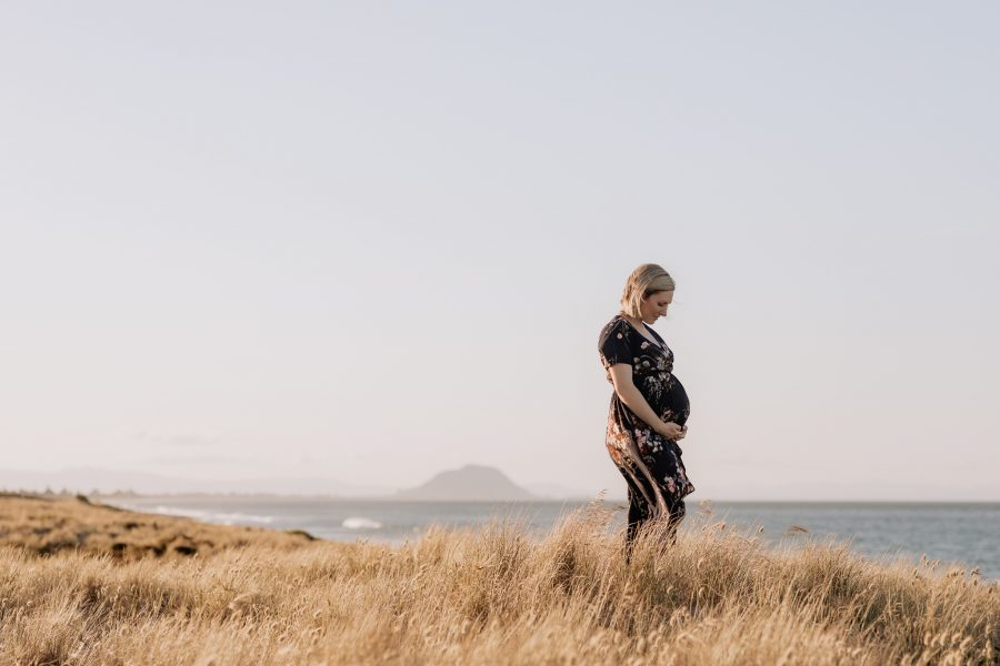 Maternity photo with Mom in sanddunes with soft tussocks around her, with the beach in the background