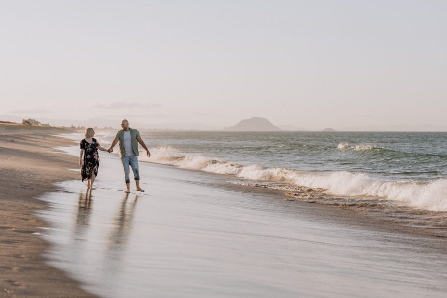 Lifestyle maternity photo of mum and dad walking on the beach waves crashing
