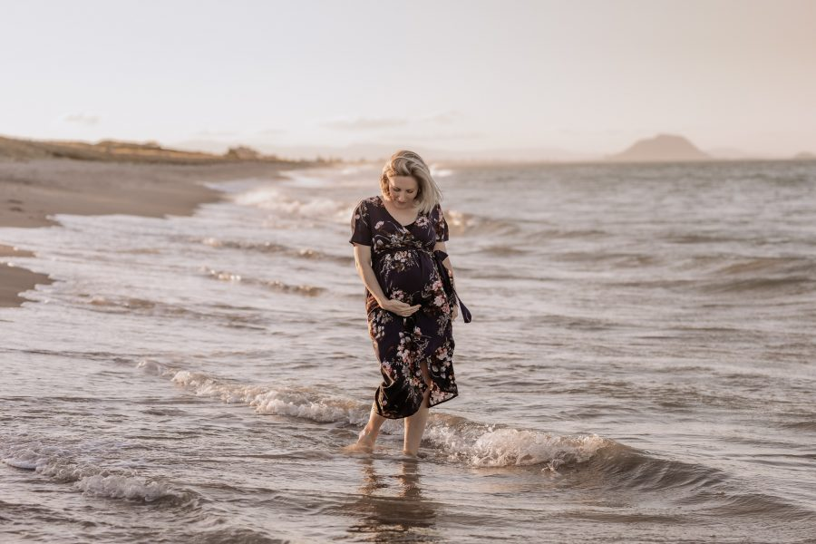 Maternity shoot of Mum walking in golden hour in the waters at Papamoa beach
