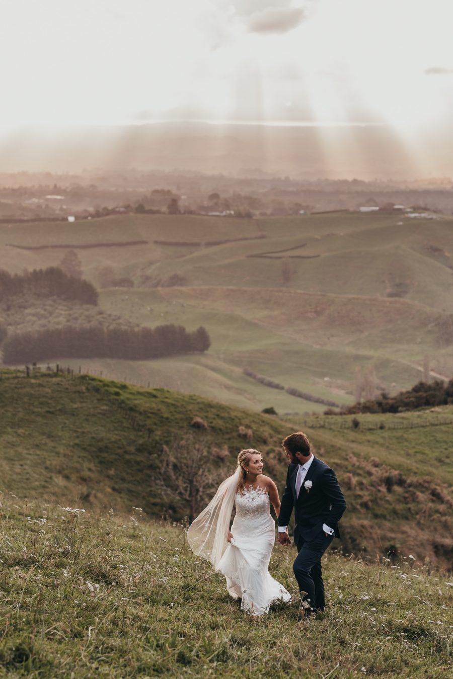 Jodi and Nick walking on their wedding day on the hills above Tauranga