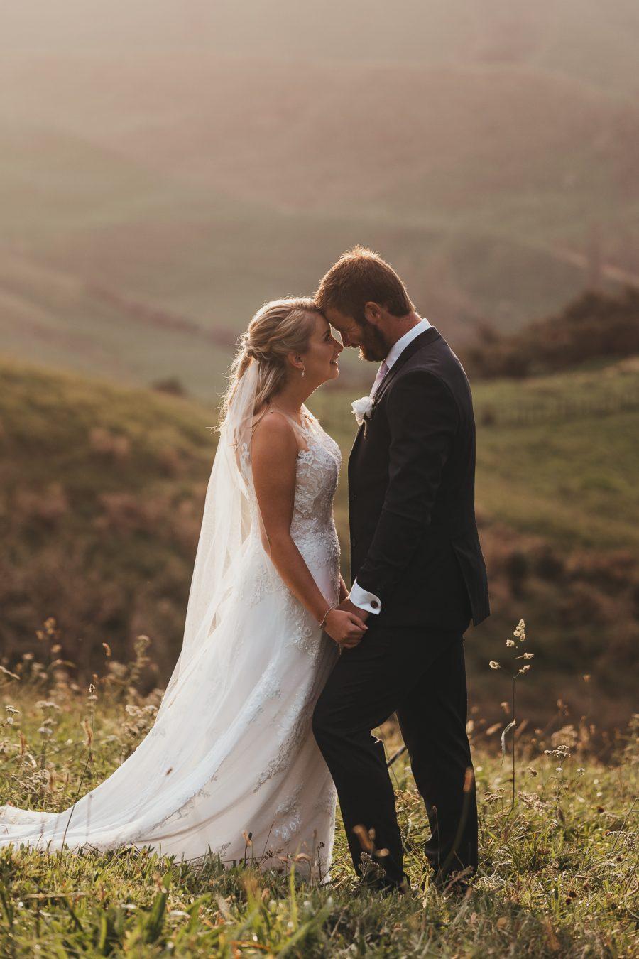Happy bride and groom at golden hour in Bay of Plenty Hills