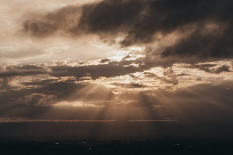 Sun coming through clouds in the evening in the hills above Tauranga