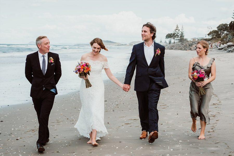 Wedding party walking the beach at Waihi