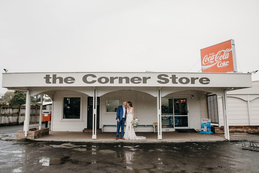Vintage Corner store on the Coromandel with Bride and groom kissing