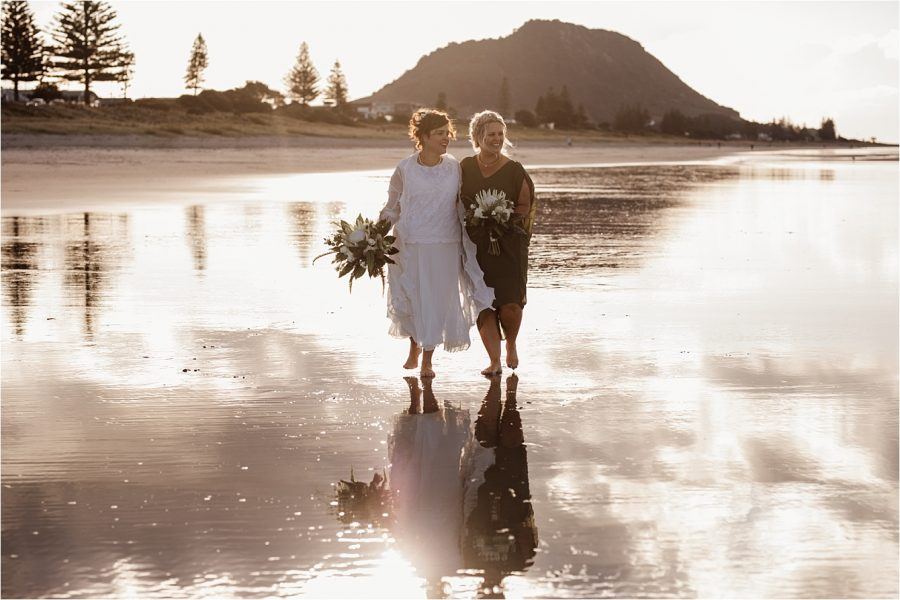 Sisters happily walking as bride and bridesmaid in sage green dress