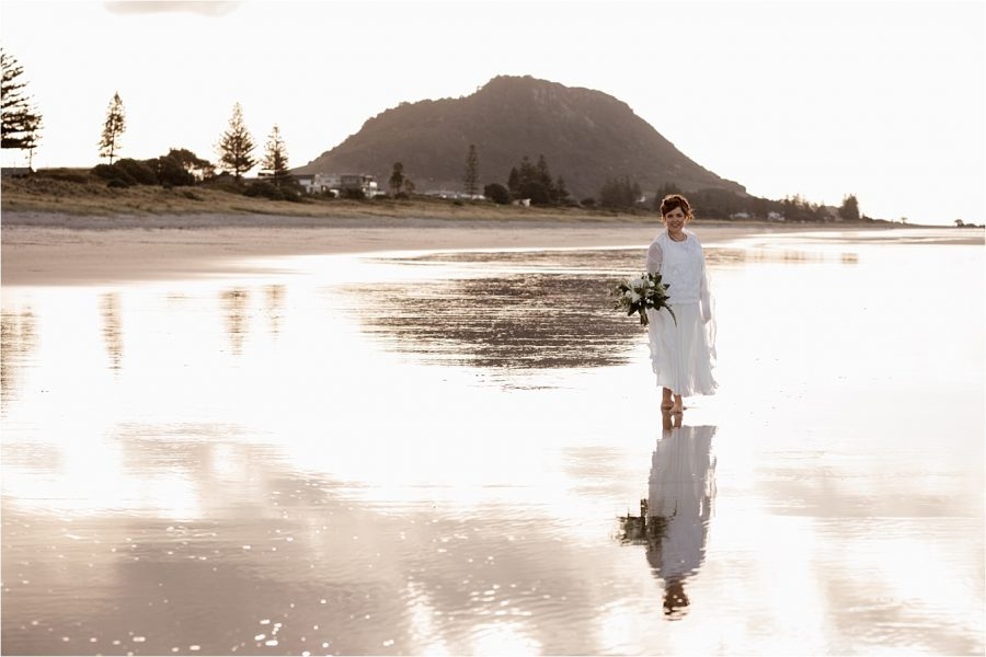 Bride on beach in golden light at Mount Maunganui