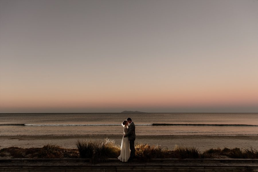 Waihi Beach sunset with wedding couple in front of beach