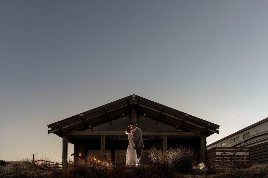 Bride and groom kissing blue light sky