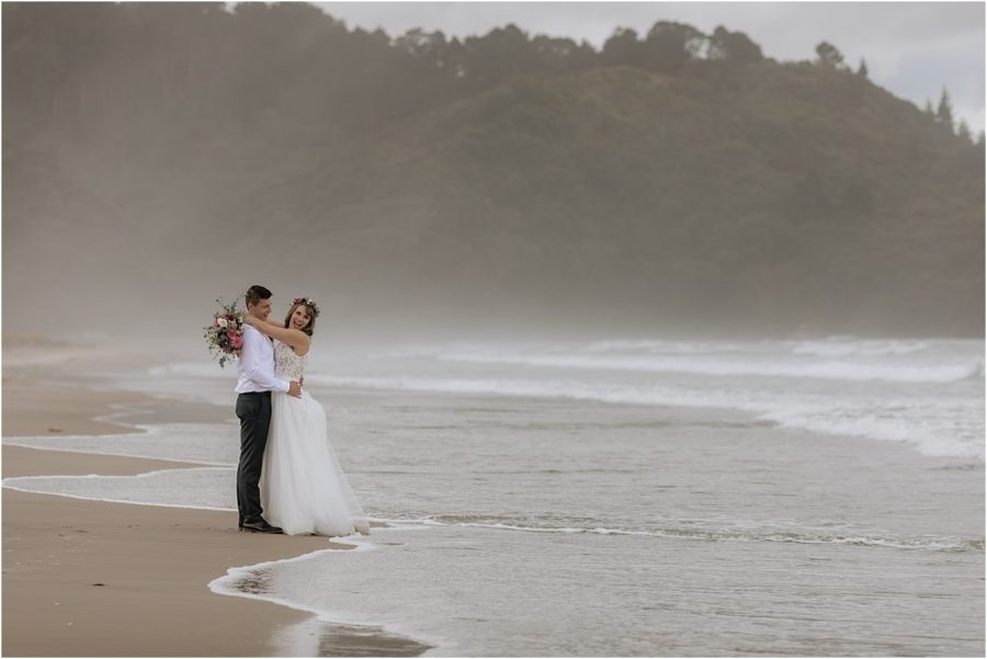 Happy couple with waves on Waihi Beach