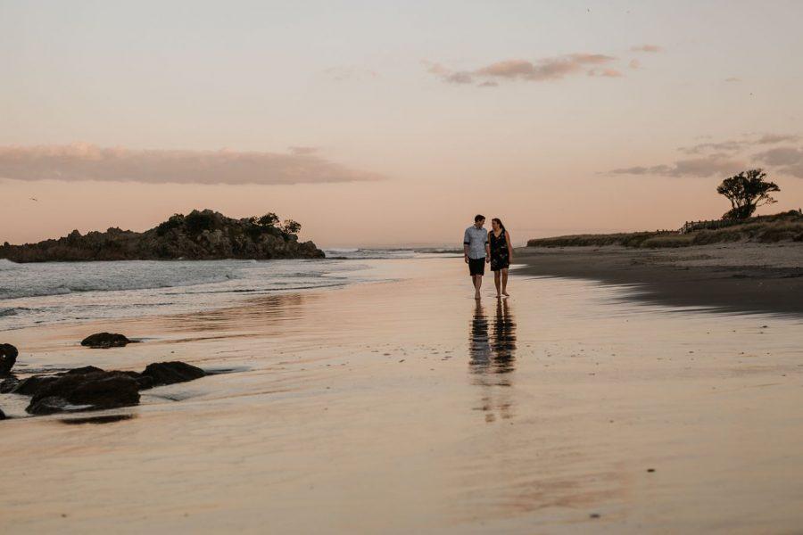Engaged couple walking on beach