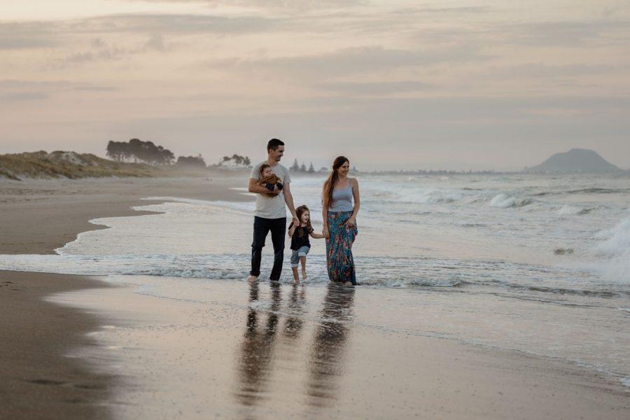 Papamoa family walking on the beach photo