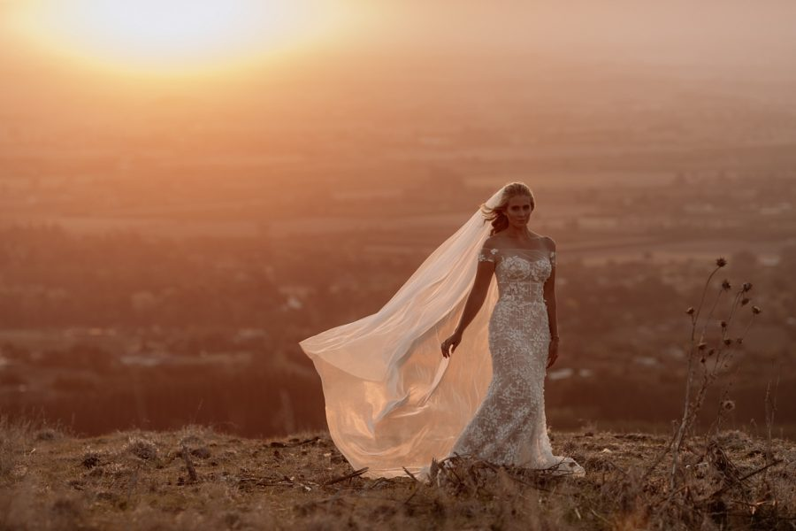 Bride on hill top at golden hour in Dellamore bridal dress