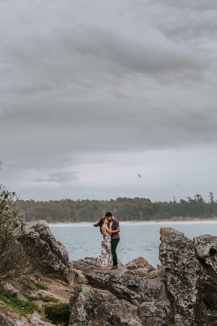 Romantic moment on rocks Tauranga engagement shoot