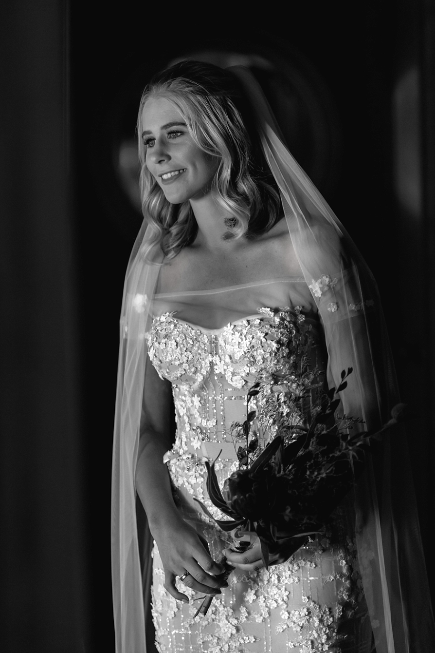Black and white image of bride in hallway before wedding