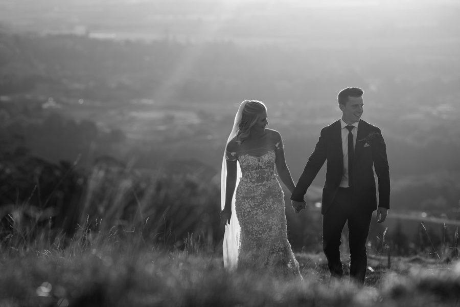 Bride and groom walking laughing up Te Mata Peak
