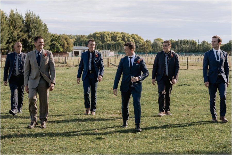 Grooms men all walking across field