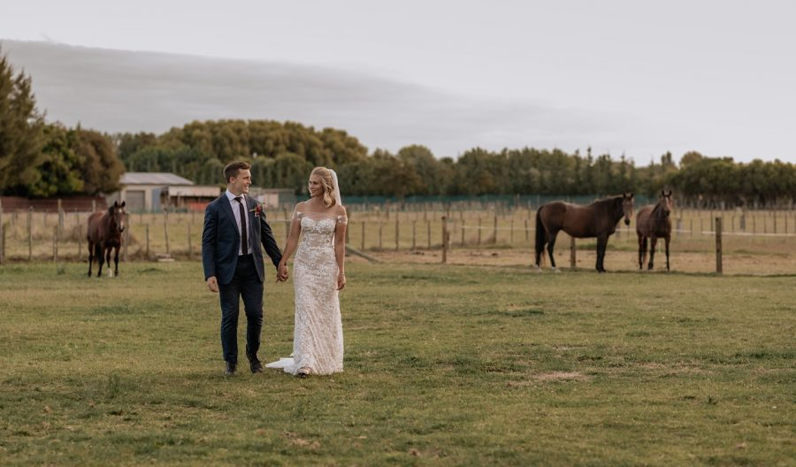 Bride and groom walking on farm with horses
