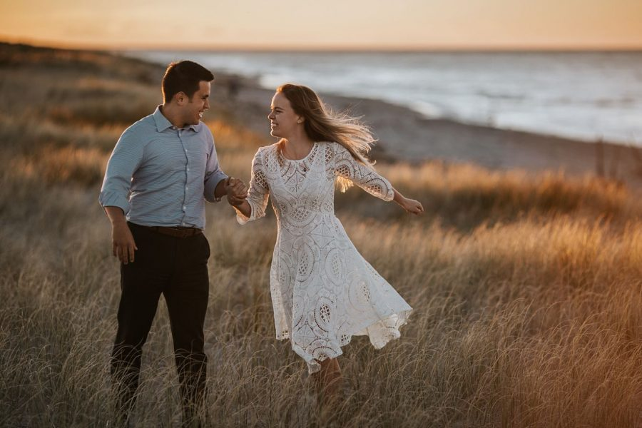happy running couple on the beach at Whakatane in golden light