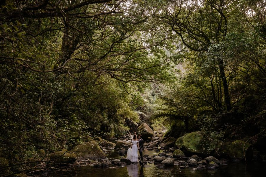 Elopement couple by stream in New Zealand