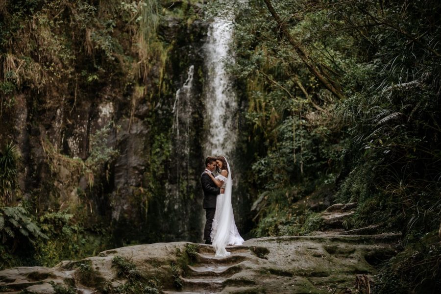 Beautiful moment in front of waterfall with bride and groom in NZ