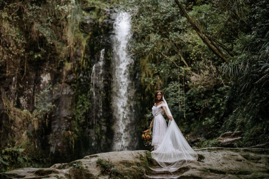 Bride in vintage dress by waterfall