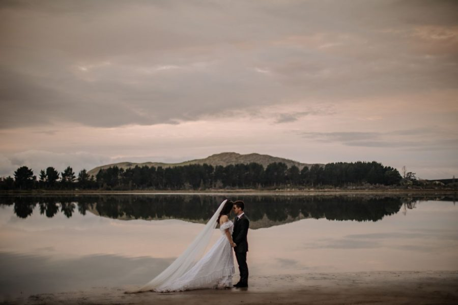 Reflections by the water in Tauranga New Zealand with elopement couple