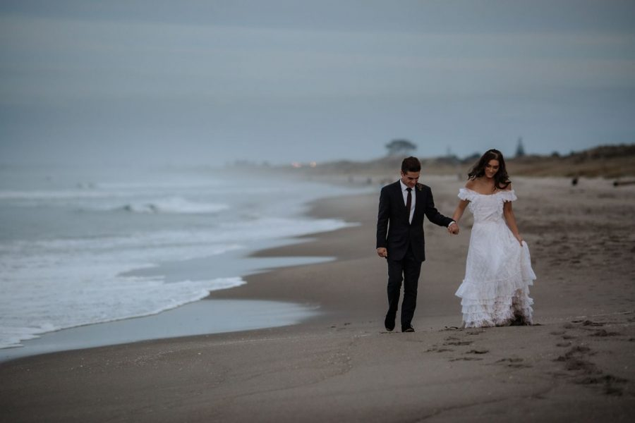 Bride and groom walking on Papamoa Beach at Winter time