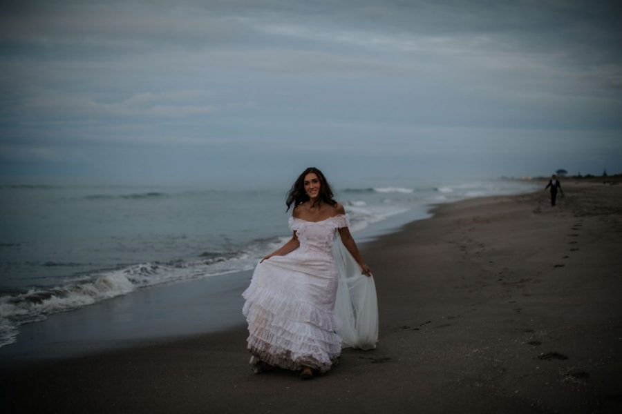 Bride walking in her boho vintage wedding dress on the beach