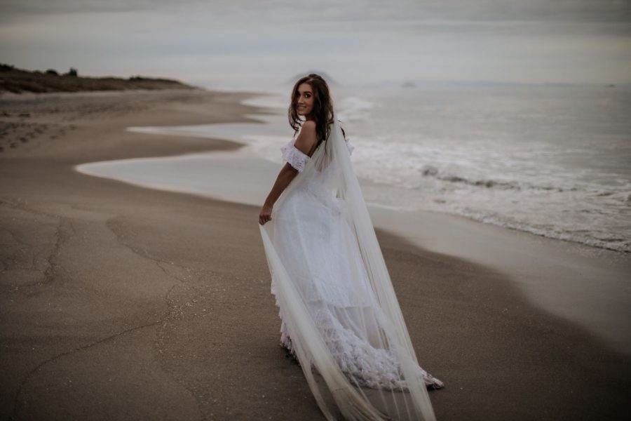 Happy natural bride walking on the beach dress dragging in the sand