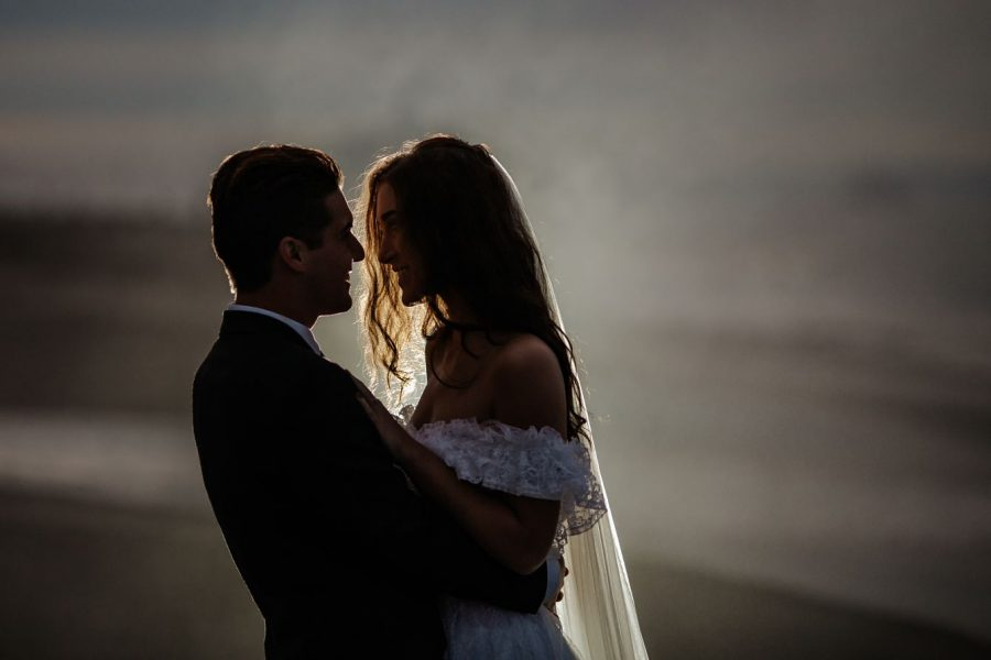 Lit up sea spray on Papamoa beach of elopement couple