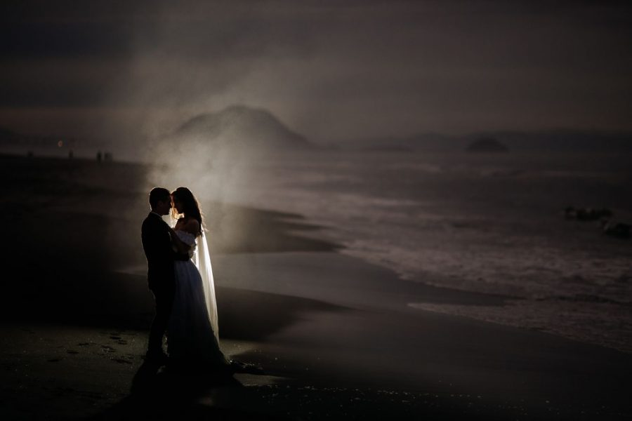 Elopement wedding waters edge beach photo lit up