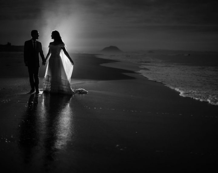 Black and white image of sea spray lit up wedding photo