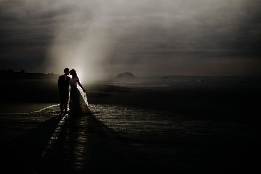 Bride and groom kissing flash shot on New Zealand beach of elopement photography