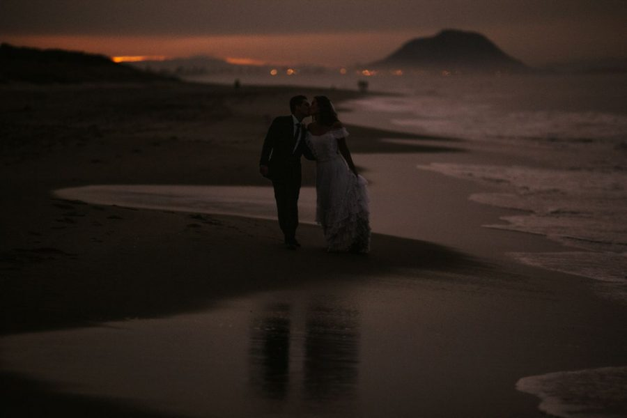 Moody wedding photo of bride and groom walking on the beach
