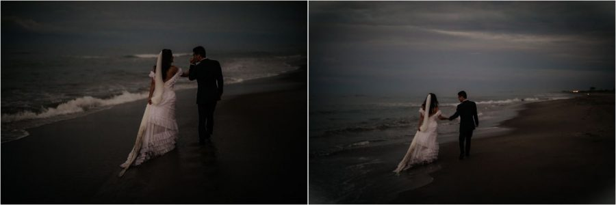 Couple end of wedding day walking into the night dress dragging in sand