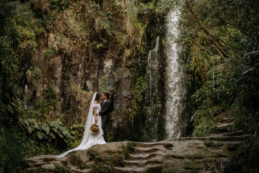Elopement couple in front of waterfall Tauranga New Zealand