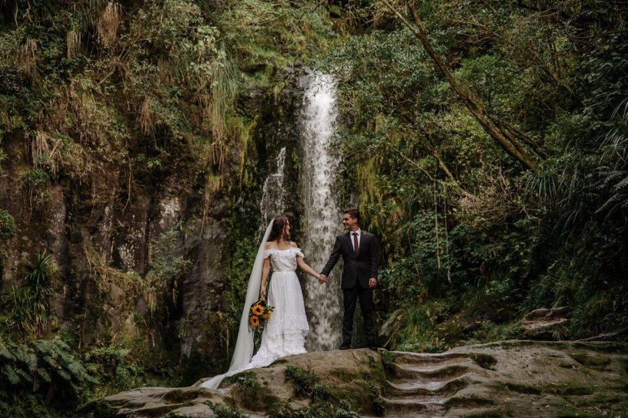 Vintage photo of bride and groom in front of waterfall