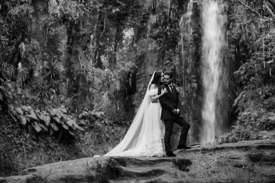 Lovely black and white photos moment elopement couple in front of waterfall