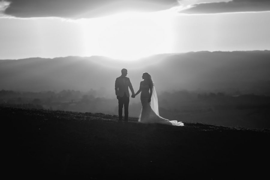 Wedding photos on top of hill with sun setting