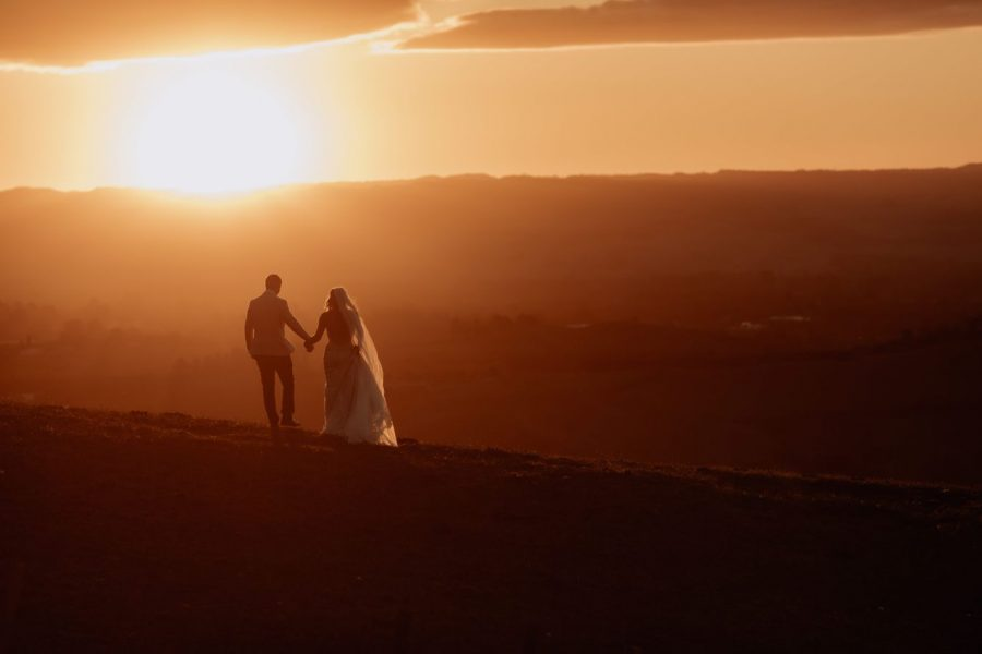 Bride and groom walking away during the sunset